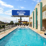 outdoor pool and exterior sign at Beachcomber Inn